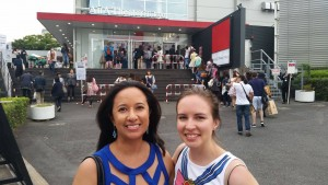 a young woman with tan skin and black hair stands with a white woman with brown hair outside the AiiA theater