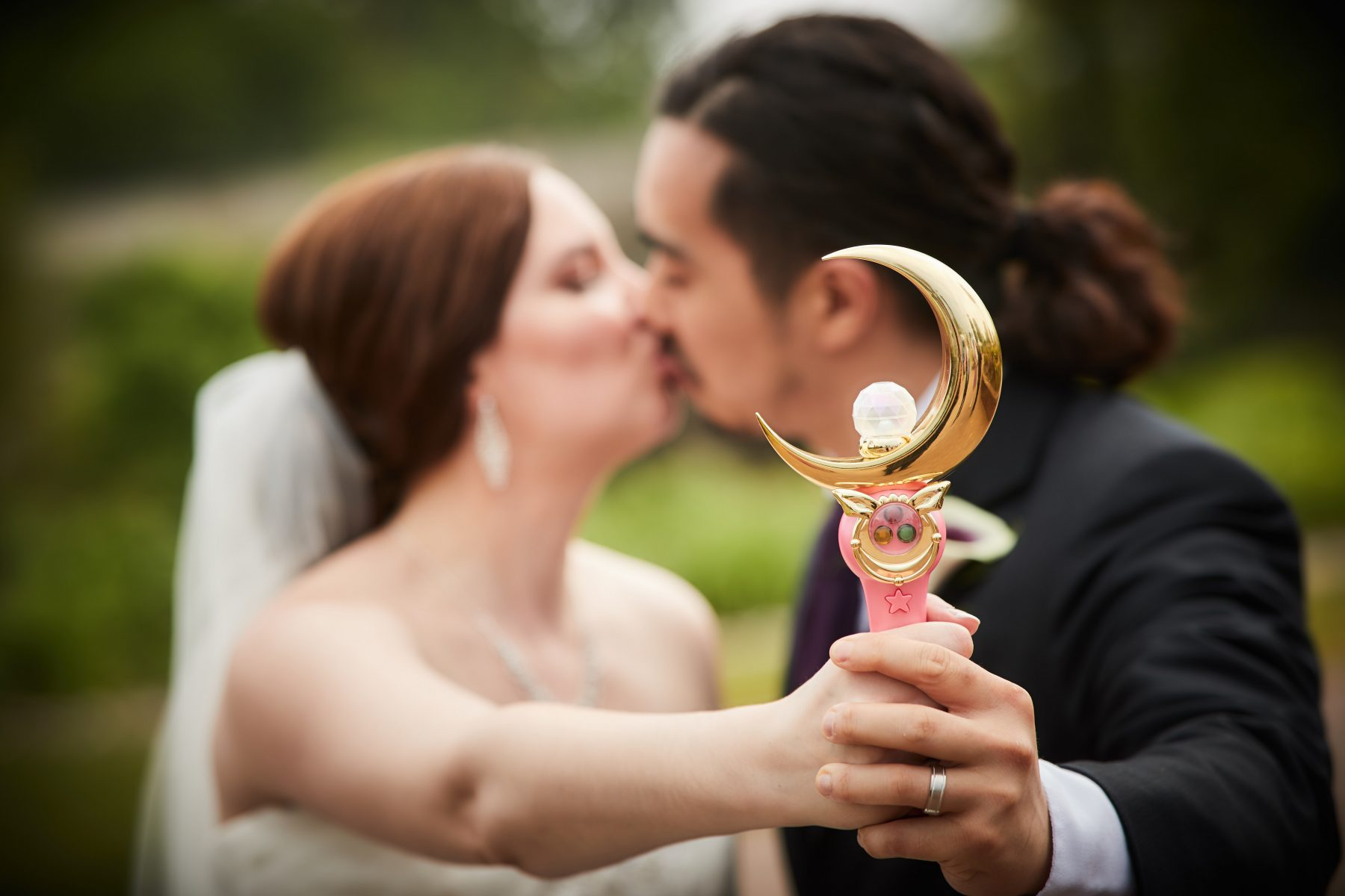 a bride and groom kiss while holding the moon stick up to the camera