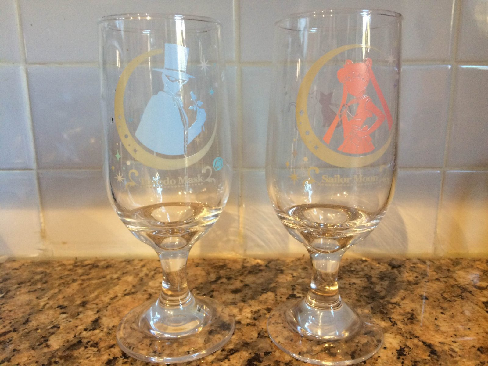 two wine glasses one with the blue tuxedo mask and another with a pink sailor moon