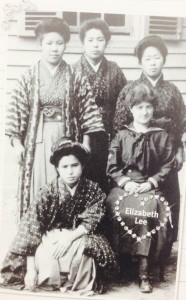 A white woman in a sailor uniform sits next to four Japanese women wearing traditional Japanese hakama.