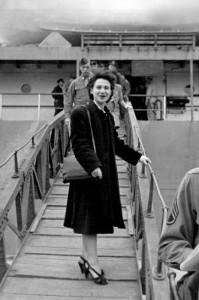 A young white woman in a long black coat stands on a ramp to a boat.