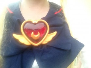 A chest shot of Usagi's crisis brooch and school uniform