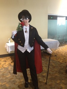 A woman stands in Tuxedo Mask cosplay