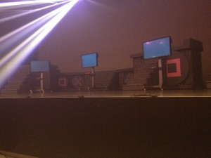 An empty stage with tv screens and video game consoles