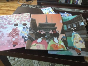 three folders sit on a table, each has a different scene with a maiko