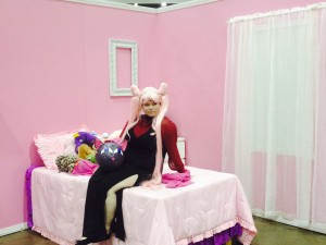 Black Lady sits on a bed in a pink bedroom