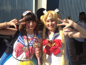 Two girls dressed as sailor moon pose for the camera. one is holding the moon scepter.