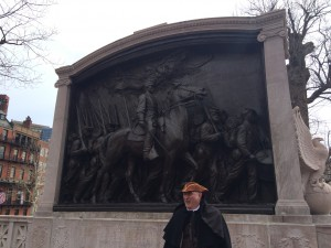 A white man dressed in period clothing stands in front of the monument of the 54th