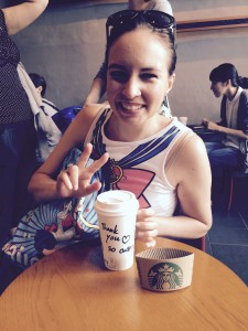 "A young white woman does the peace sign while her starbucks cup reads ""Thank you so cute!!"""