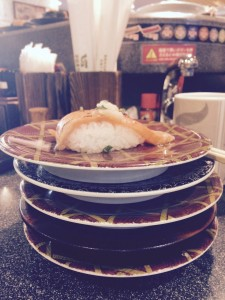 A piece of sushi sits atop five plates
