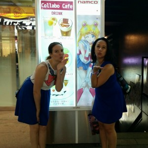 Two young women stand inf front of the Sailor Moon cafe, blowing kisses like Sailor Moon