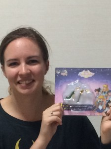 A young white woman holds a package with two Sailor Jupiter charms