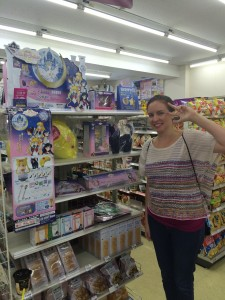 A young white woman poses infront of a Sailor Moon ichiban kuji display
