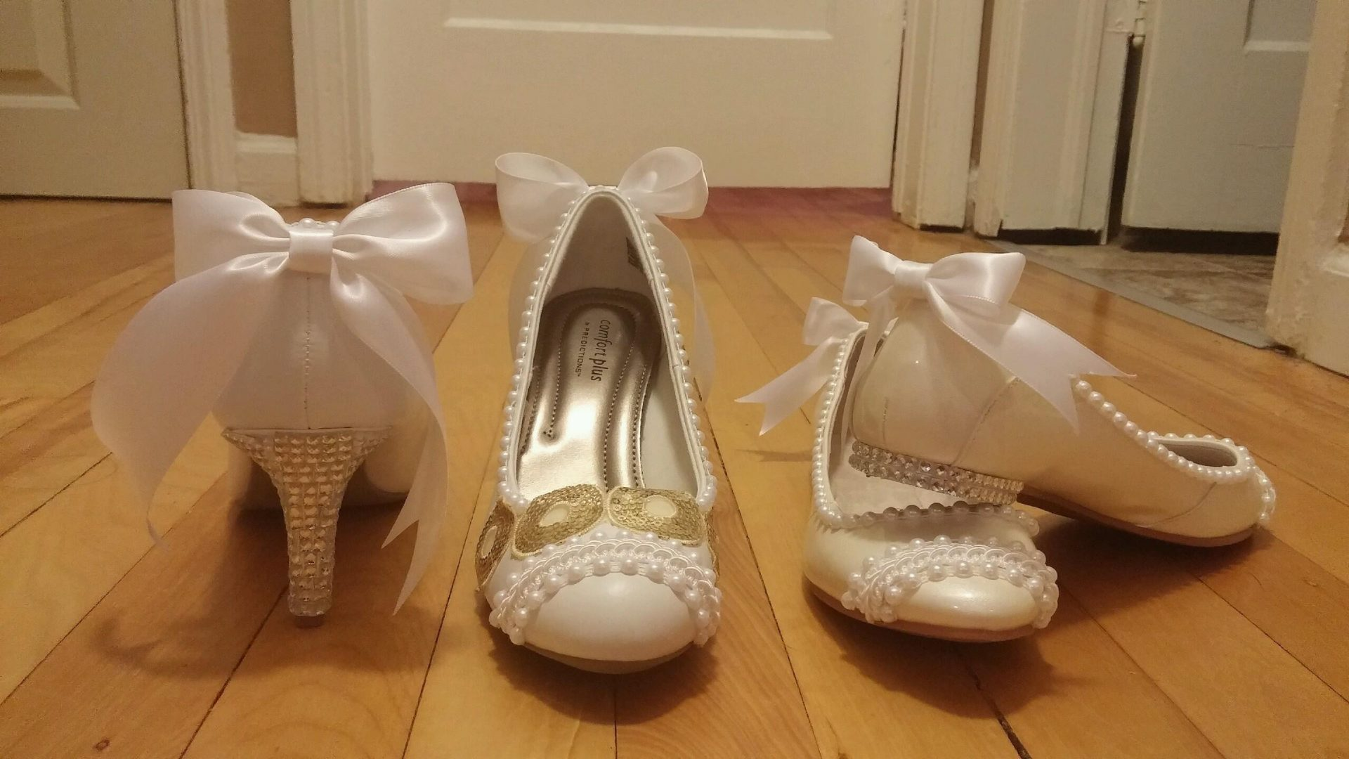 two sets of white shoes one with heels and another flats with pearls and white bows