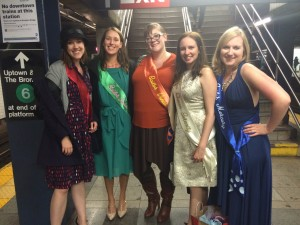 Five young women stand in sailor guardian colors at a train station