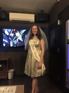 A young woman in a silver dress and white veil stands in front of a TV with an image from Gundam Seed