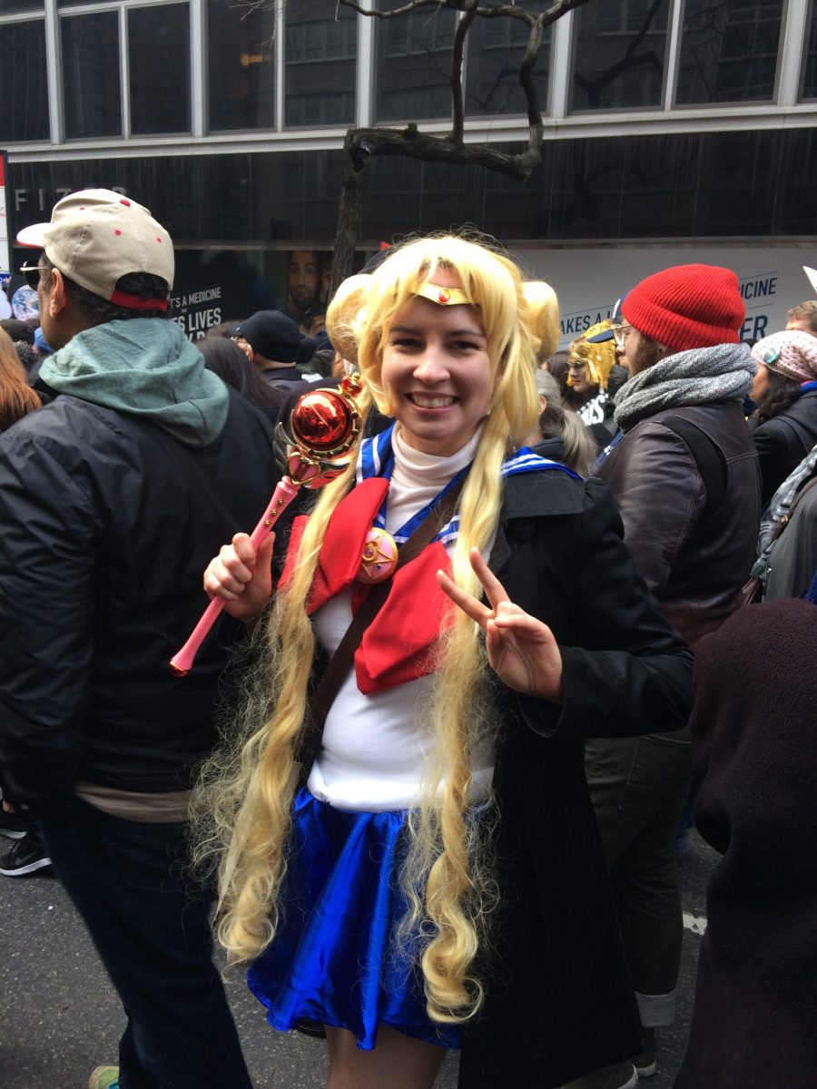 Sailor Moon stands in a crowd holding the cutie moon rod