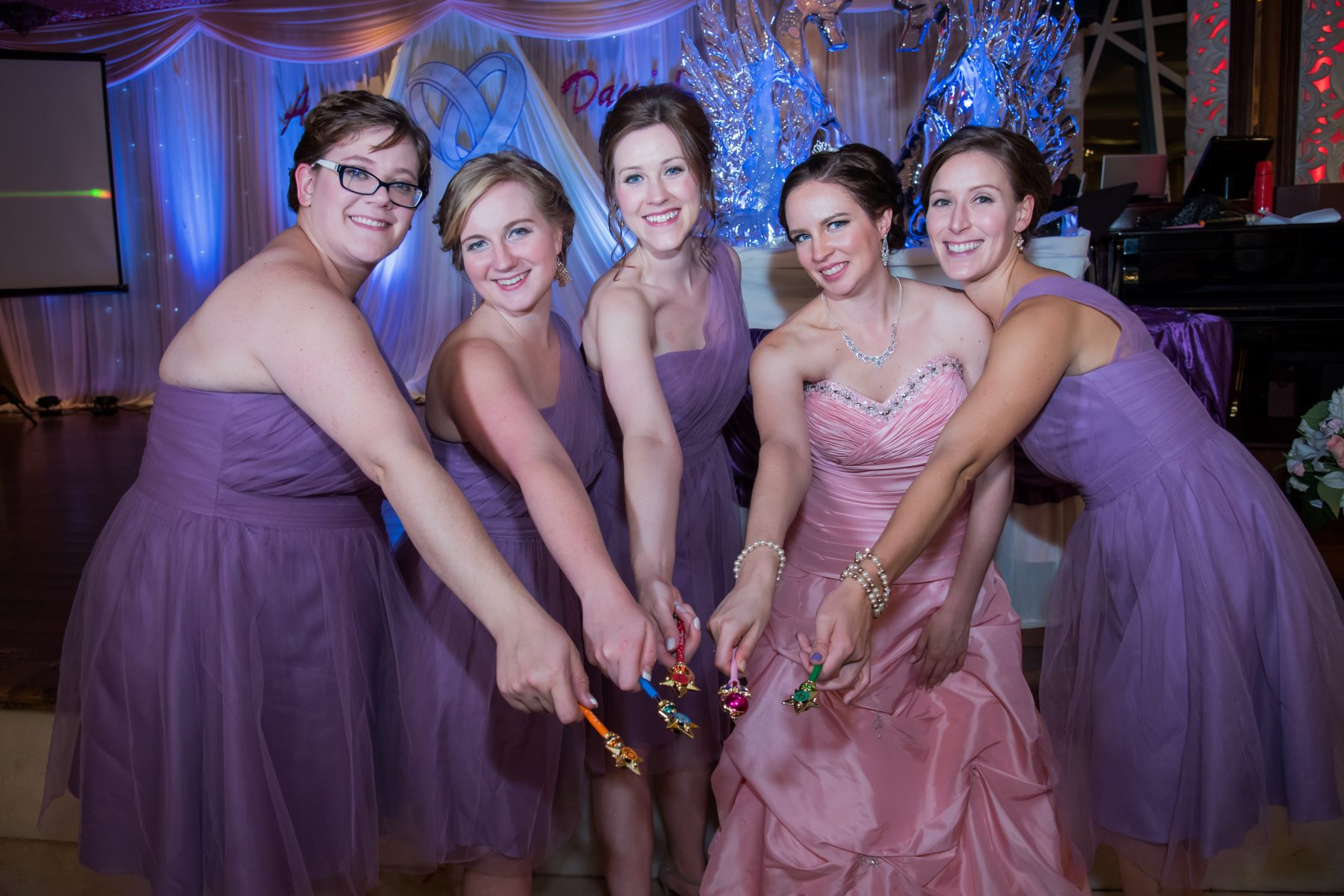four young white women in lavendar dresses stand around a young white woman wearing a poofy pink dress, all holding sailor moon transformation pens