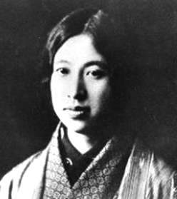 A black and white photo of a young Japanese woman wearing several layers of kimono.