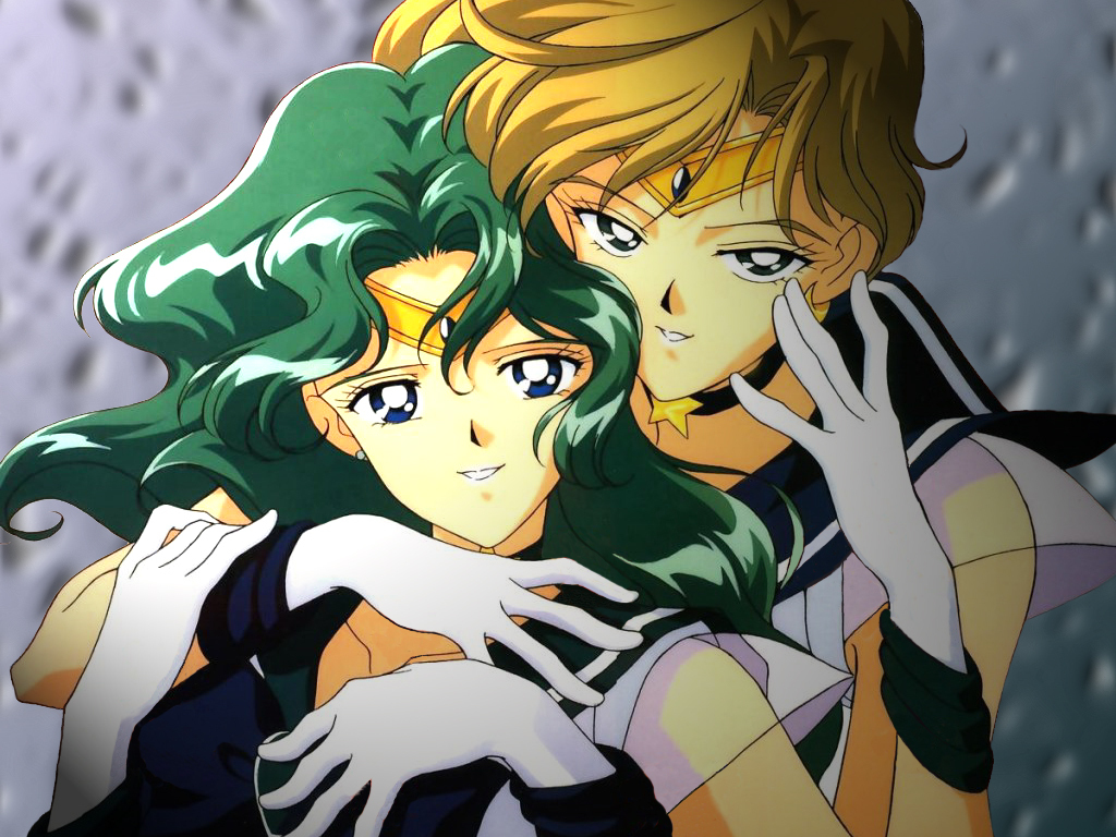 A blonde woman has her arms wrapped around a woman with aqua hair