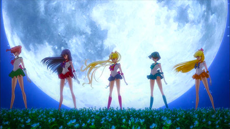 opening shot of the first opening credits of sailor moon crystal with the five guardians standing in front of a white moon in a field of blue flowers