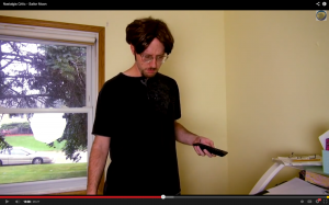 Nostalgia Critic stands holding a remote wearing a black t-shirt and pimples on his face.