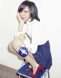 Avu-chan wearing a white shirt with a blue skirt with red heels with a Luna P ball