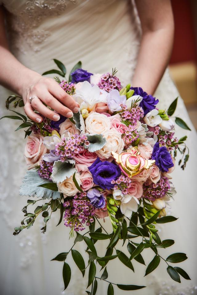 a pink and purple wedding bouquet with a crisis brooch in it.