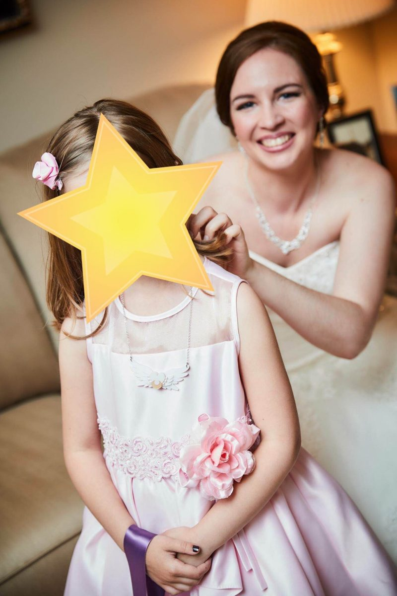 a bride fixes a necklaces on a young flower girl wearing pink