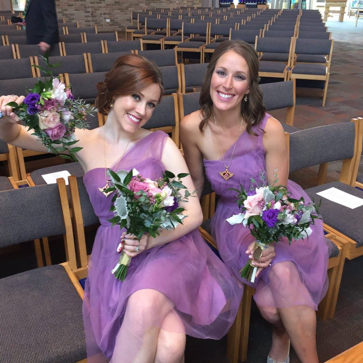 two bridesmaids sit on grey colored chairs holding their bouquets