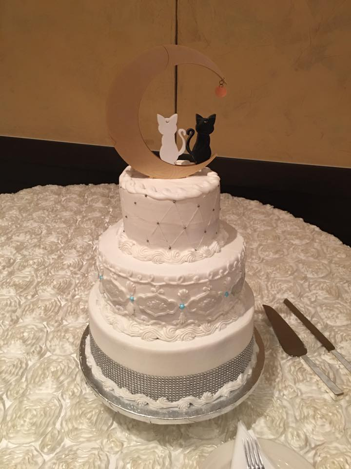 A white three tiered cake with a gold crescent moon topper with luna and artemis