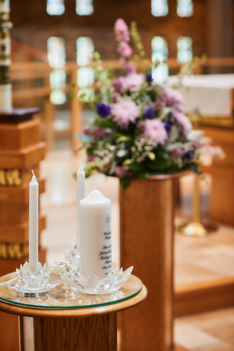 a unit candle and two taper candles sit in crystal lotus holders with purple flowers in the background