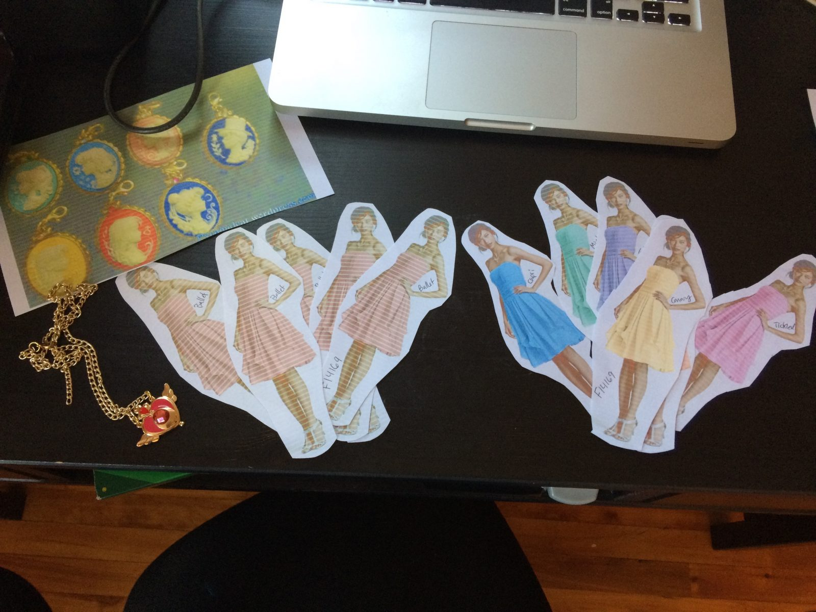 cutouts of models wearing various brideamaids dresses and colors with a photo of sailor moon cameos and crisis compact necklace