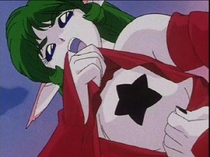 A woman with green hair and a red outfit reveals a black star on her breast