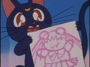 Luna holds up a drawing of a fat Sailor Moon