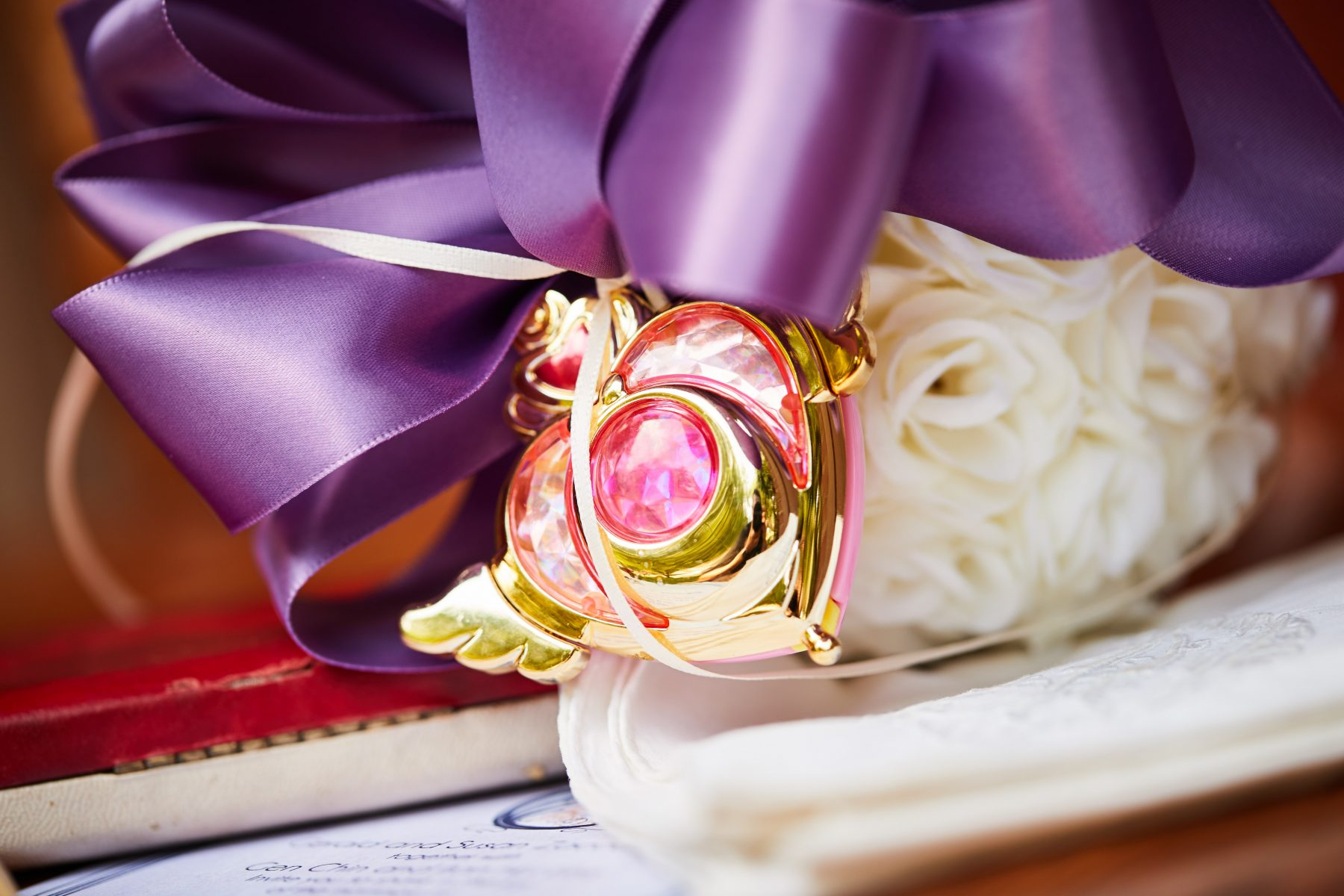 the crisis compact hangs on a white flower ball with a purple ribbon