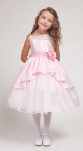 a little white girl stands wearing a pink layered flower girl dress