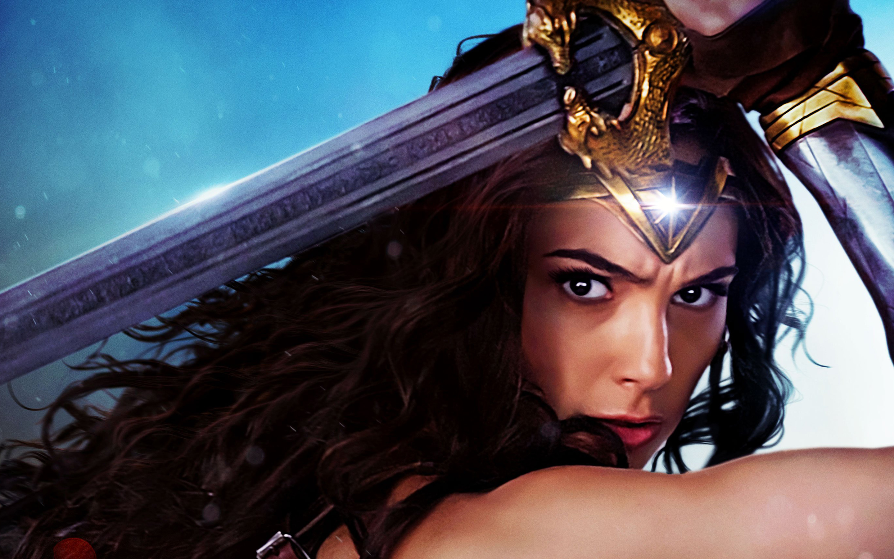 Wonder Woman holds her sword over her head, looking serious. The star in her tiara gleams.