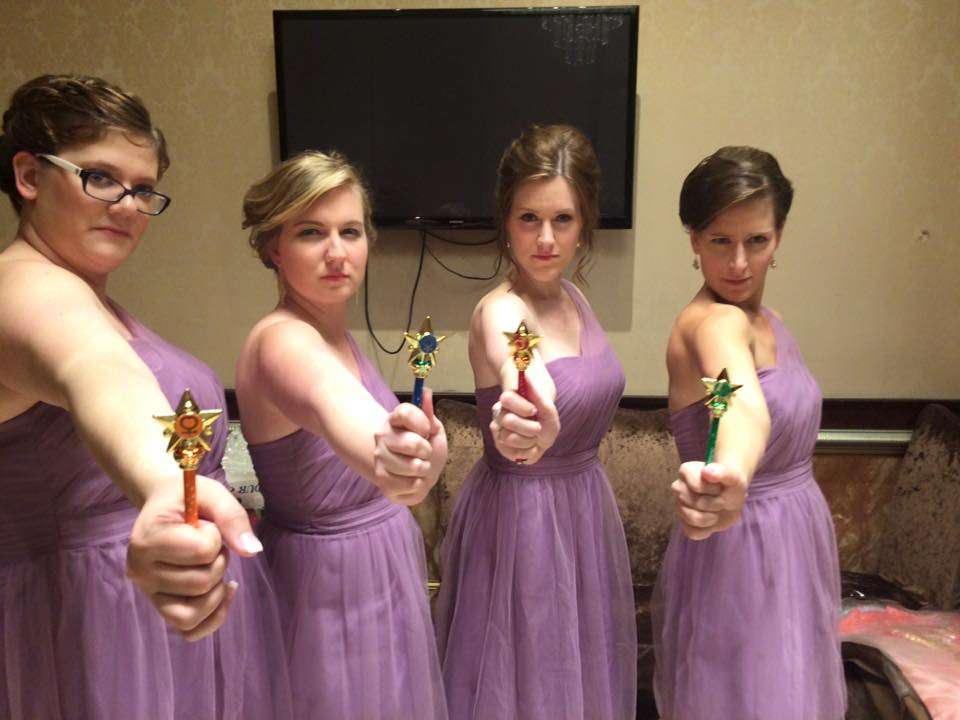 four young women in purple dresses looking very serious with transformation wands