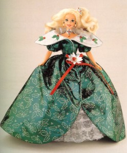 A blonde barbie wears a long beauitufl green dress with a holly berry motif