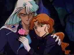 A man with long white hair hugs a man with long orange hair