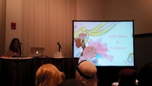 A young white woman sits at a table with a mic with a big screen next to her with the words Sailor Moon & Feminism