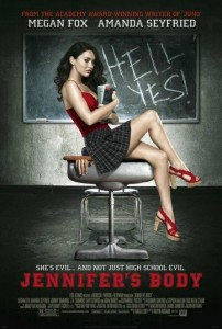 """Jennifer sits on a desk in front of a blackboard the says """"hell yes!"""""""