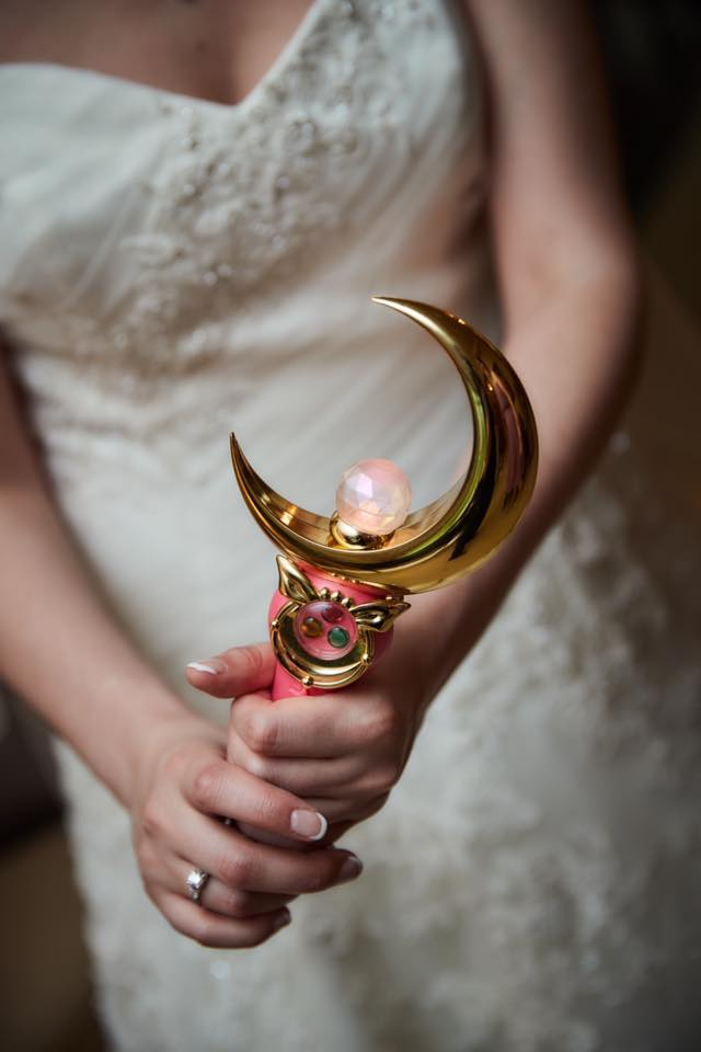 a bride holding a proplica moon stick