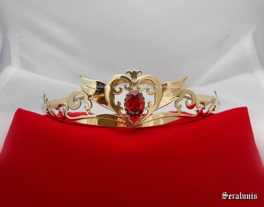 a gold tiara with a red jewel sitting on a red velvet pillow