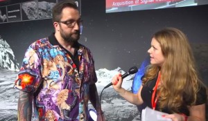 A bearded white man wearing a shirt with very sexy white women on it stands next to a young woman with a microphone