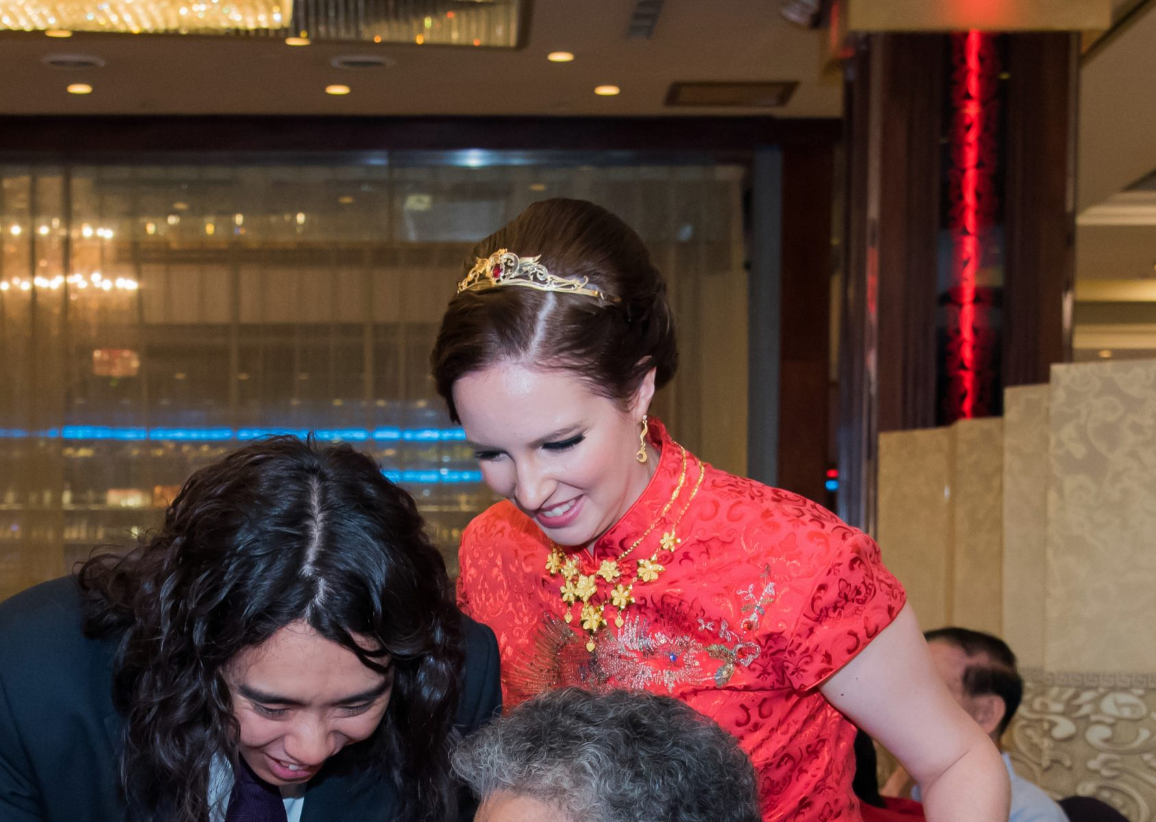 a young white woman wears a red qipao with a gold flower necklace, gold earrings and a gold tiara with a red stone