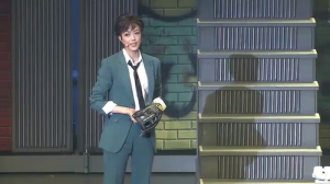 Yuuga as Mamoru stands in a green suit with a black tie with a baseball glove.