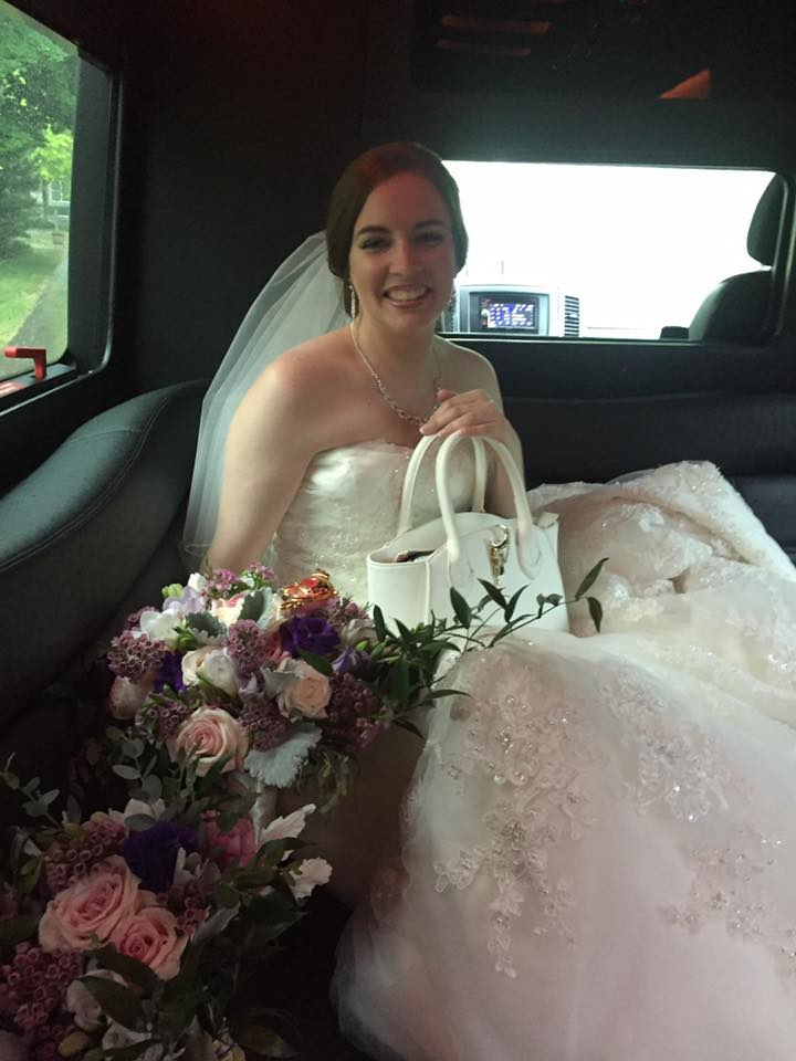 a bride sits in car with a white sailor moon bag