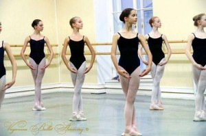 Young ballerinas stand, posed, wearing black leotards and white tights.